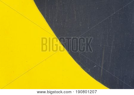 Abstract detail of wall with fragment of graffiti, old chipped paint, scratch, grunge texture. Aerosol design, black-yellow colors. Modern background, pattern, wallpaper or banner design