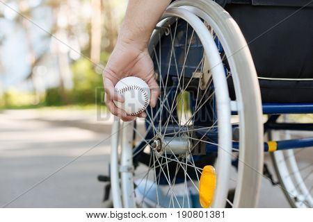 Do not give up. Wheelchair for disabled people being on the foreground where young man sitting and going for walks