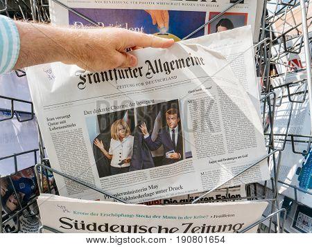 PARIS FRANCE - JUN 12 2017: Man point of view buying at press kiosk Frankfurter Allgemeine Zeitung newspaper with photos of Emmanuel Macron and Brigitte Macron voting for the French legislative election 2017