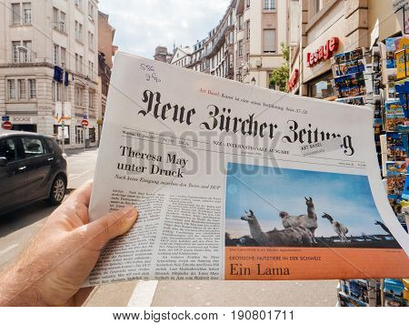 PARIS FRANCE - JUN 12 2017: Man point of view personal perspective buying at press kiosk Neue Burcher Zeitung newspaper with Theresa May elections in United Kingdom