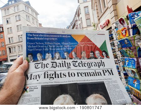 PARIS FRANCE - JUN 12 2017: Man point of view personal perspective buying at press kiosk The Daily Telegraph newspaper with reactions to United Kingdom general election of 2017 - May fights to remain PM
