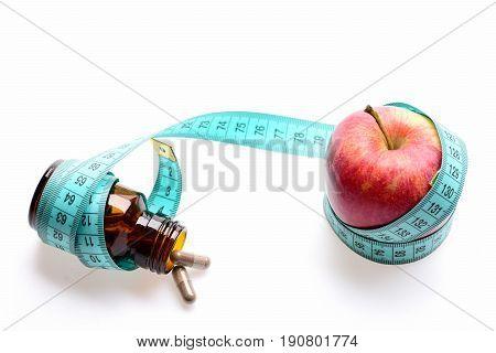 Concept of vitamins diet and nutrition: red apple and bottle with pills wrapped around with greenish blue measuring tape isolated on white background