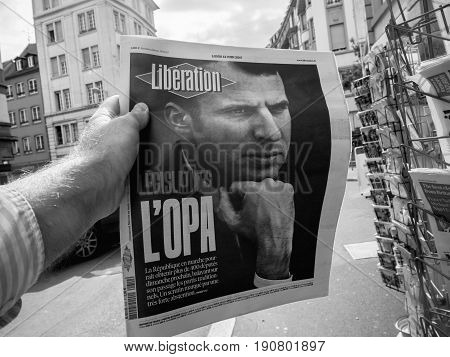 PARIS FRANCE - JUN 12 2017: Man point of view personal perspective buying at press kiosk French newspaper Liberation with portrait of Emmanuel Macron after French legislative election 2017 - black and white