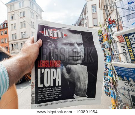 PARIS FRANCE - JUN 12 2017: Man point of view personal perspective buying at press kiosk French newspaper Liberation with portrait of Emmanuel Macron after French legislative election 2017