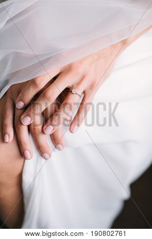 Bride's morning. young beautiful bride in white wedding dress and veil puting hand together on a knee. engagement ring with big diamond. wedding nail concept.