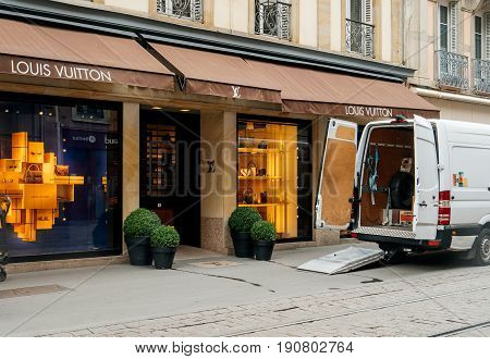 STRASBOURG FRANCE - JUN 12 2017: Wite delivery van suppling stock with clothes parcels and accesories a windows of the Louis Vuitton store on empthy shopping street