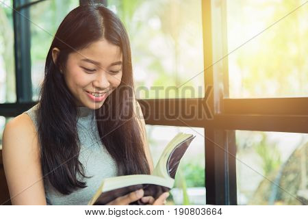 Enjoy relax times with reading book Asian women Thai smile with book in coffee shop vintage color tone