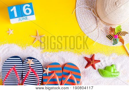 June 16th. Image of june 16 calendar on yellow sandy background with summer beach, traveler outfit and accessories. Summertime concept.