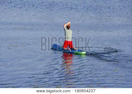 Man on Paddle Board paddling out to lake