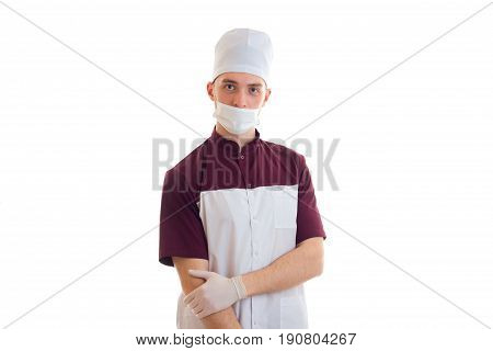 young strong Laboratory Assistant with the mask on the face and in the medical Cap looks into a camera close-up of isolated on white background.