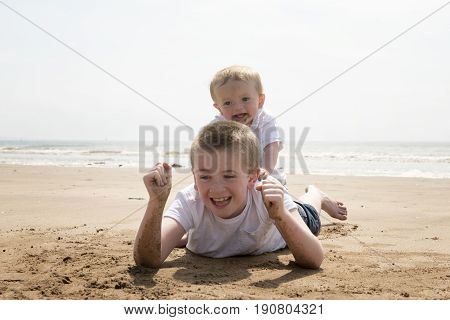 Ten year old boy with his baby brother playing on the beach
