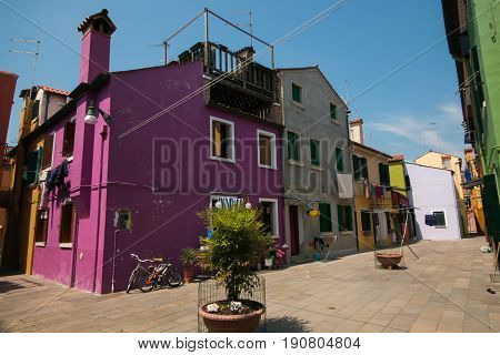 BURANO, ITALY - MAY 23, 2017: Square with colored houses in the historic center of Burano