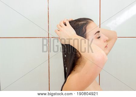 Portrait of a young brunette who is standing under the shower with wet hair closeup