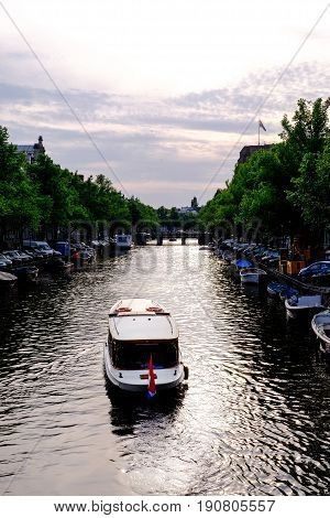 pleasure boat on canal in amsterdam in the evening