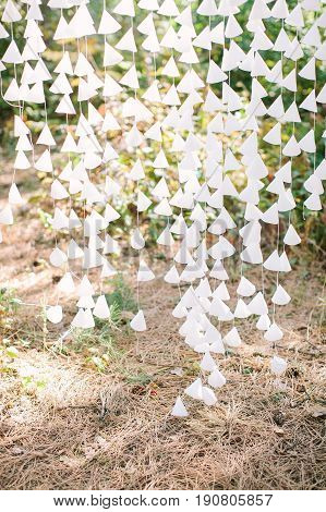 white paper cone elements strung on thread as a part of a wedding decor , outdoor. nature recreation, date, engagement, romantic, event concept.