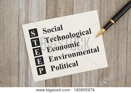 STEEP Social Technological Economic Environmental Political text on a card on weathered wood and a pen