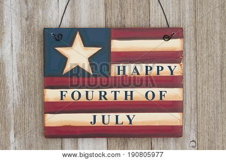 Happy 4th of July text on a retro USA flag wood sign on weathered wood