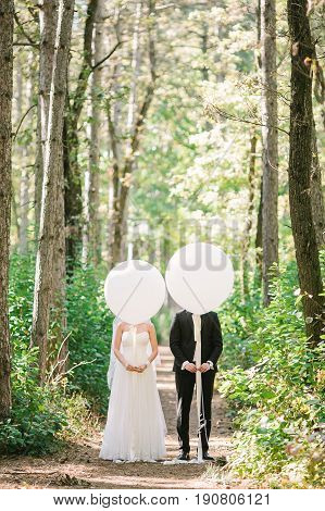 Newlyweds couple with white balloons. Funny photo with bride in a white wedding dress and groom in a black suit. Newlyweds have covered the faces with white balloons on forest background.