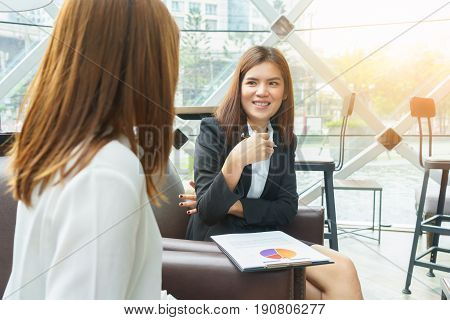 Smiled business woman talking and thinking about their work - business meeting conceptSmiled business woman talking and thinking about their work - business meeting concept