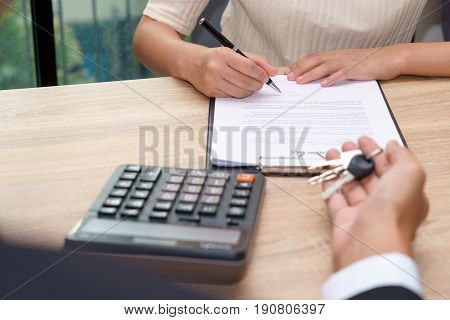 Businessman giving key and customer signing loan agreement document with calculator on wooden desk