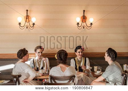 NOVI SAD SERBIA - JUNE 11 2017: Young women wearing a traditional Serbian costume having a drink in a local cafe