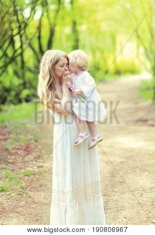 Happy young mother is tenderly kissing her baby holding on the hands in a spring day