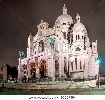 Basilica of Sacre Coeur at night, Paris, France. Long exposure shot with tourists on the stairs.