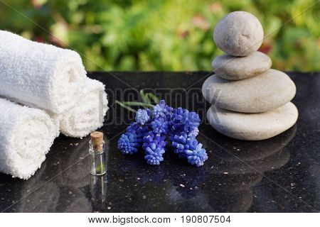 Set for spa procedures, massage stones, white terry towels and blue flowers Mischures on a polished granite table in the garden.