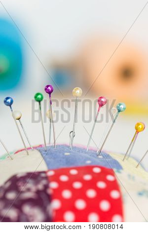 closeup sewing tools, patchwork, tailoring and fashion concept - macro with colorful stitched pincushion and many beautiful pins, background skeins of pink and blue thread, selective focus, vertical