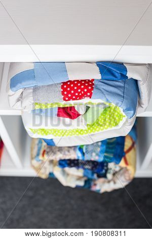 patchwork, sewing and fashion concept - two colorful finished quilted bedspreads in the studio at white shelves with few storage compartments, the warehouse of finished products, top view.