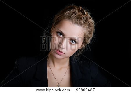 Portrait of the girl in a suit on a black background