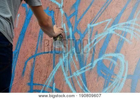 A Hand With A Spray Can That Draws A New Graffiti On The Wall. Photo Of The Process Of Drawing A Gra