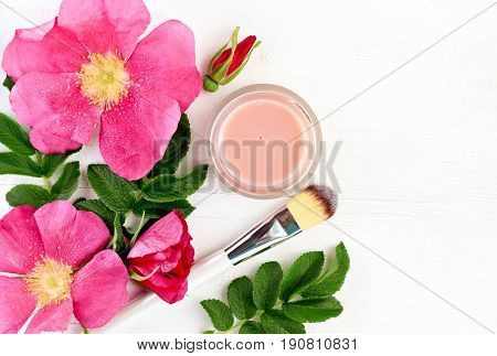 Wild rose extract botanical beauty treatment. Fresh pink flowers, jar of facial mask, top view white wooden table.