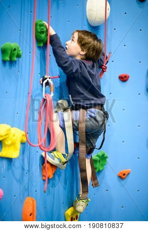 A little boy climbing a rock wall indoor