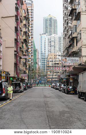 KOWLOON HONG KONG - APRIL 21 2017: Skyscraper and Empty Street at Morning in Kowloon Hong Kong.