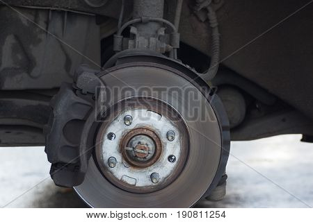 Car without wheel waiting for tyre wheel replacement at service road assistance