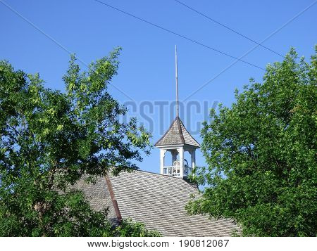 The old rural country School House Bell tower against the blue sky.