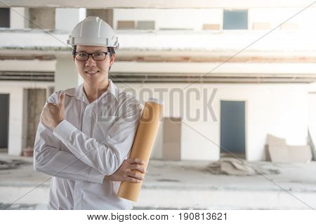 Young Asian Engineer or Architect holding architectural drawing while wearing personal protective equipment safety helmet at construction site. Engineering Architecture concepts