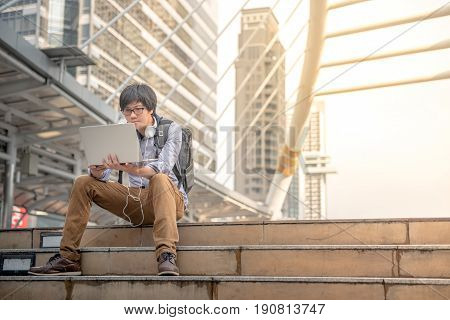 Young Asian business man dressed in casual style working with laptop computer in the city digital nomad lifestyle and working outdoor concepts