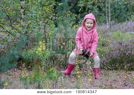 Happy little girl is dancing with binoculars in hand