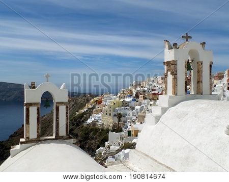 Greek islands traditional church bell-towers and the impressive landscape of Oia village, Santorini island, Greece