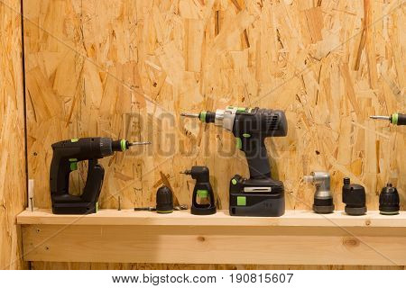 Set of screwdrivers adapters bits nozzles on wooden shelf and background.