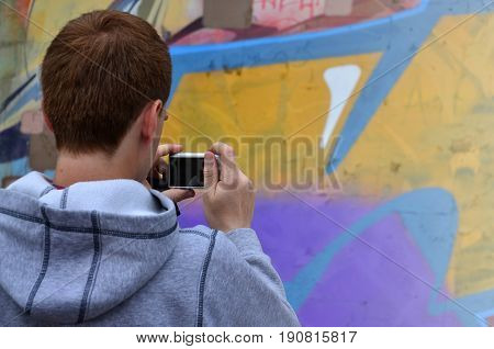 A Young Graffiti Artist Photographs His Completed Picture On The Wall. The Guy Uses Modern Technolog