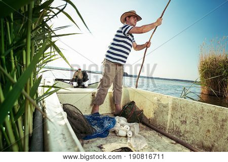 Fisherman pushing boat from the river bank