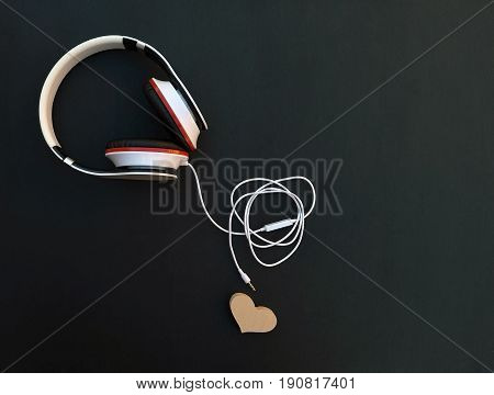 Musical accessories on a dark background. Headphones and heart. The connector is not connected. Concept / Loneliness / Listen to your favorite tunes / Collapse of relationships /