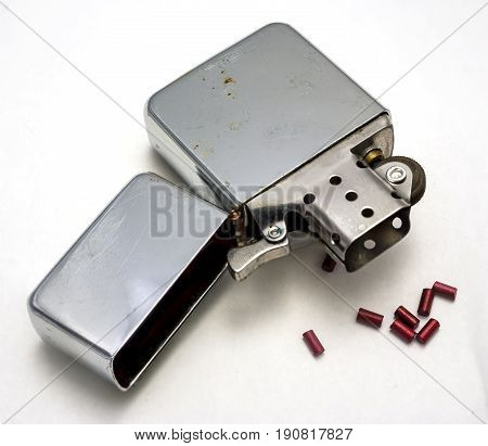 cigarette lighter opened with beads of reserve flint white background
