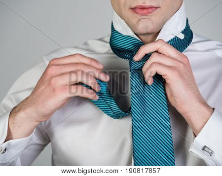 Man Tying A Striped Tie In White Shirt
