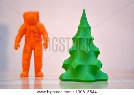 The model printed on a 3d printer. The object in the form of an orange cosmonaut and a green Christmas tree stands on a table. Progressive modern additive technology. Copy spase, spase for text.