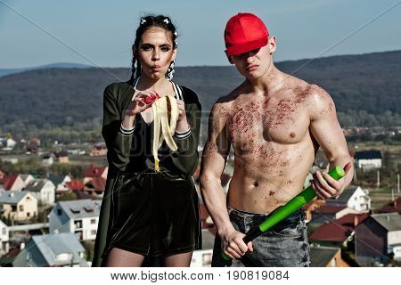 woman or cute girl eating banana fruit. Man or athlete in red cap with bronze powder on torso skin holding baseball bat. Mountain landscape. Health and sport vegetarian diet healthy dieting