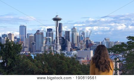 SEATTLE, WASHINGTON STATE, UNITED STATES - OCTOBER 10, 2014: Skyline panorama view from Kerry Park during the day, woman watching the city.